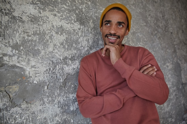 Pensive pretty young bearded male with dark skin holding his chin with raised hand and looking upwards positively, wearing pink sweater and mustard cap