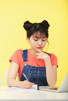 Pensive pretty young woman writing in copybook when doing math homework and solving equations