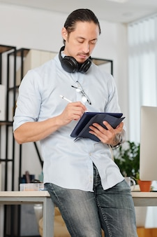 Pensive professional graphic designer with headphones around his neck leaning on office desk and drawing on digital tablet