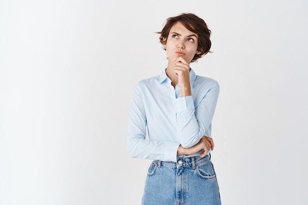 Задумчивая профессиональная женщина смотрит вверх и думает, задумчиво стоит на белой стене в синей рубашке с воротником