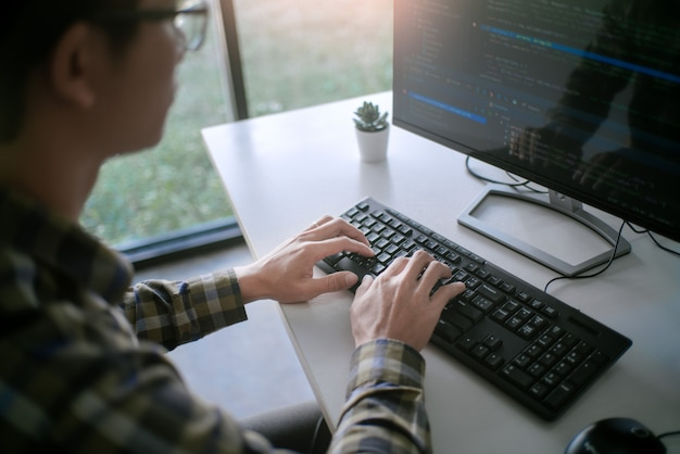 Задумчивый программист, работающий над технологиями программного кода для настольных пк или над дизайном сайта в офисе software development company