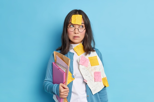 Pensive puzzled schoolgirl prepares for exams at school bites lips and concentrated aside tries to learn information before math test wears round glasses for vision correction.