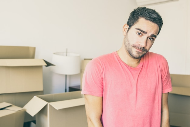 Pensive puzzled young man moving in new apartment, standing in front heap of opened carton boxes