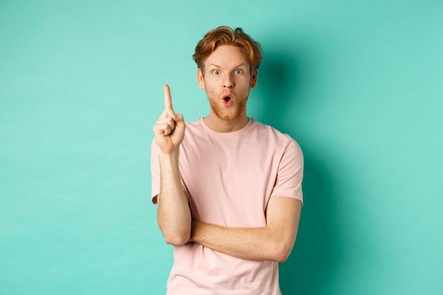 人差し指を上げるtシャツの物思いにふける赤毛の男、アイデアを投げながらあえぎ、提案を言って、ターコイズブルーの背景の上に立って