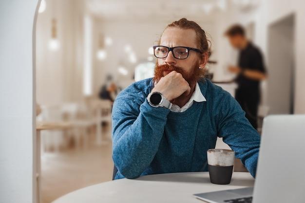 Задумчивый рыжий человек, работающий на ноутбуке в кафе