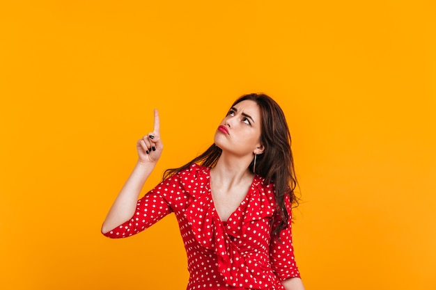 Pensive sad brunette in red top shows finger up. portrait of girl on isolated yellow wall.