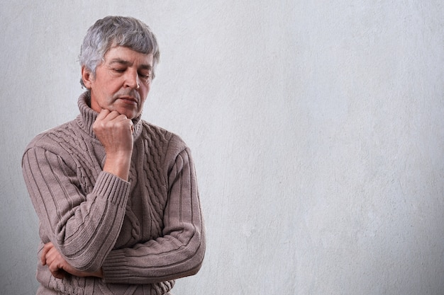 Pensive sad mature man holding his hand under his chin looking down with unhappy expression thinking about something