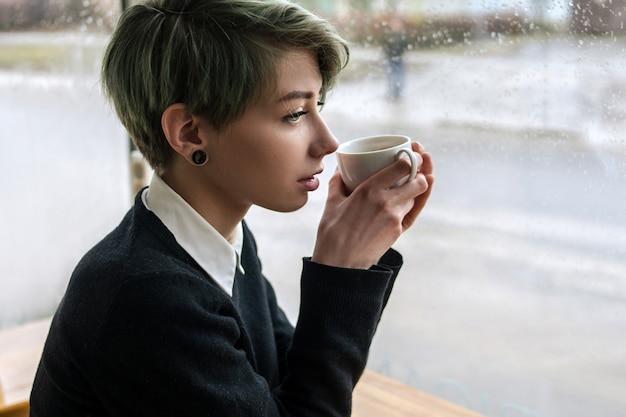 커피 한 잔을 들고 잠겨있는 슬픈 사려깊은 어린 소녀. 정서적 스트레스 또는 사랑 드라마 개념을 경험하는 여성