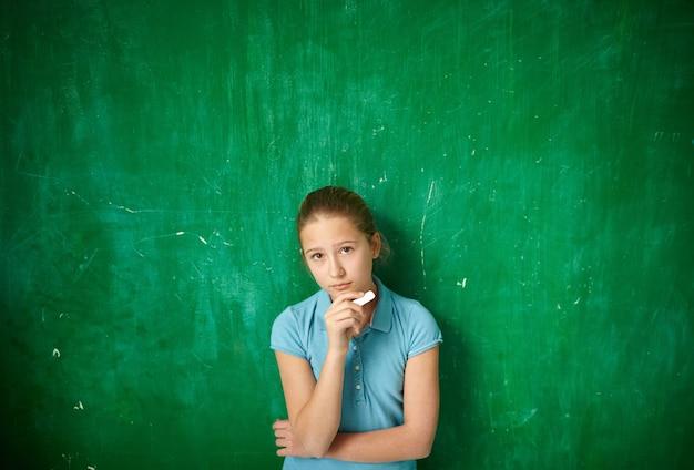 Pensive schoolgirl with blackboard background