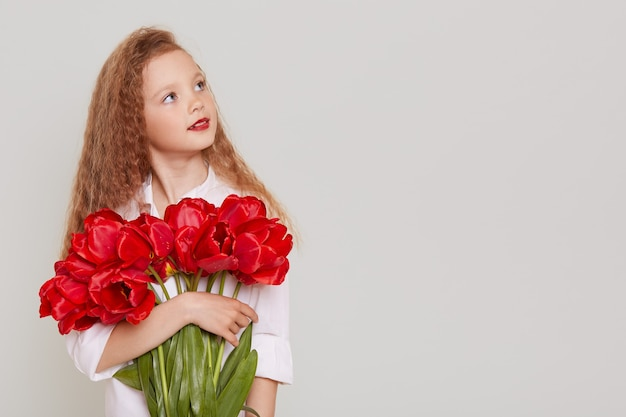 Pensive schoolgirl with blonde wavy hair looking away with thoughtful facial expression, holding big bouquet of red tulips