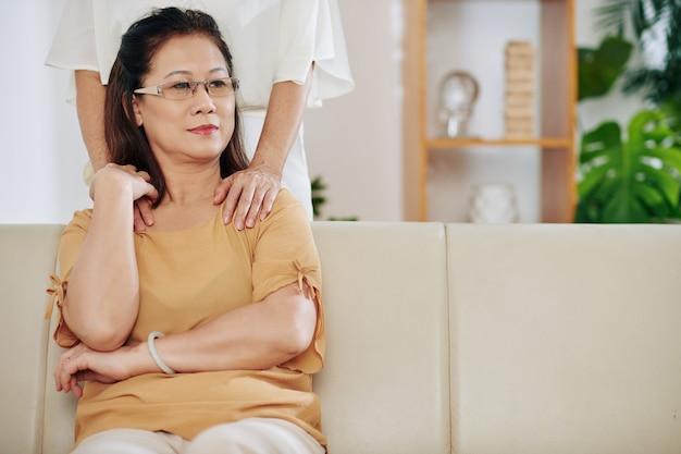物思いにふける年配のアジア人女性が自宅のソファに座って、彼女の友人が彼女の肩に触れて、彼女を安心させてサポートしようとしています