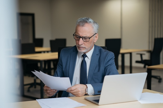 Pensive senior businessman reading contract. portrait of handsome male working with documents in office