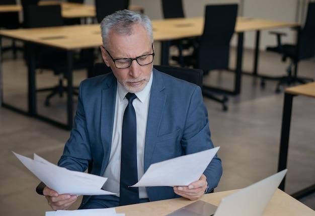 財務報告を読んで物思いにふけるシニアビジネスマン