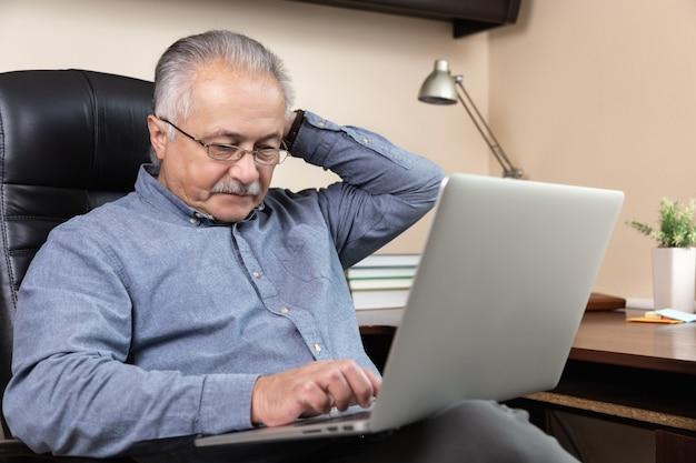 잠겨있는 수석 사업가 집에서 작동합니다. 안경을 쓴 노인이 노트북을 사용하여 원격으로 일하고 있습니다. coronovirus 개념 중 원격 작업