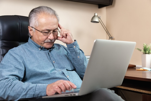 Pensive senior businessman work at home. an elderly man in glasses is working remotely using a laptop. remote work during coronovirus concept