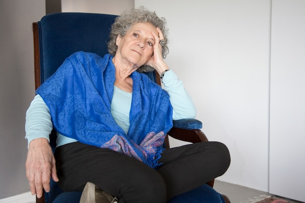 Pensive senior lady sitting in rocking chair and looking away