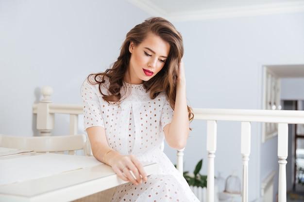 카페 테이블에 앉아 생각에 잠겨있는 관능적 인 젊은 여자