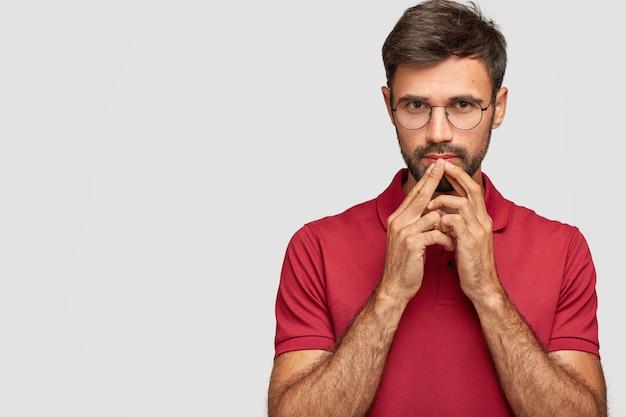 Il maschio barbuto serio pensieroso tiene le mani vicino alla bocca, contempla qualcosa, vestito con una maglietta rossa, sta contro il muro bianco