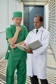 Задумчивые серьезные врачи читают результаты медицинских анализов и анамнез пациента и обсуждают возможный диагноз.