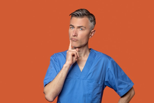 Pensive smart man in medical clothes