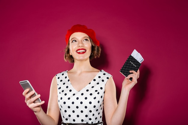 Pensive smiling ginger woman in dress holding smartphone and passport with tickets while looking up over pink