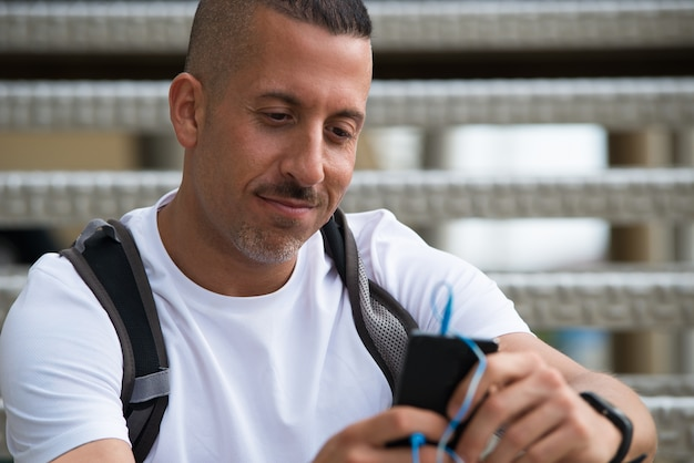 Pensive smiling man surfing net on smartphone