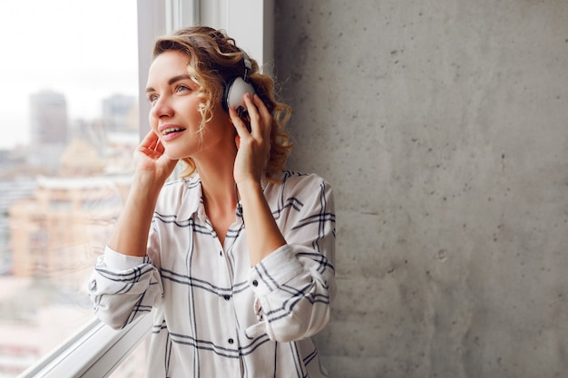 窓の近くでポーズをとって、物思いにふける笑顔の女性がイヤホンで音楽を聴きます。モダンなインテリア。