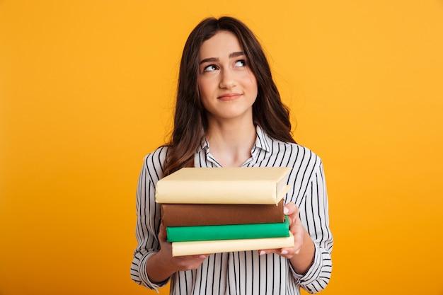 Donna sorridente pensierosa nei libri e nel cercare della tenuta della camicia