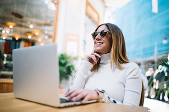 Задумчивый улыбается молодая женщина, используя ноутбук за столом в уличном кафе