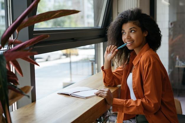 Задумчивый студент учится, подготовка к экзамену, держа перо. портрет молодой фрилансер работает из дома