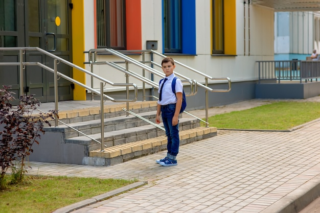 白いシャツ、青いネクタイ、バックパックを身に着けた物思いにふけるスタイリッシュで若い男子生徒は、色とりどりの窓で学校の背景に立っています