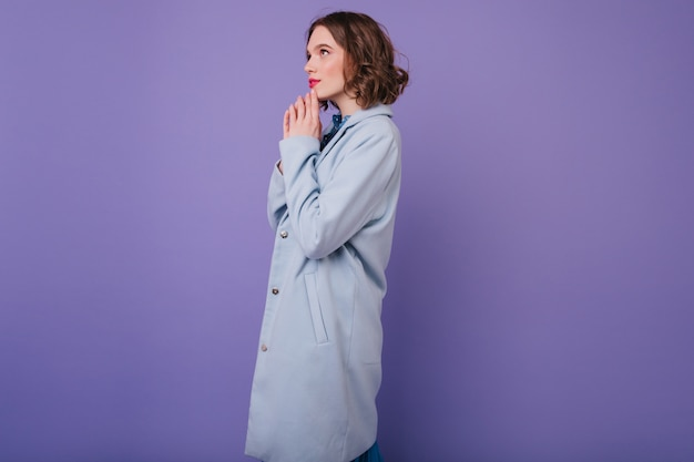 Pensive stylish woman in long blue coat posing . indoor photo of pretty short-haired lady in autumn attire.