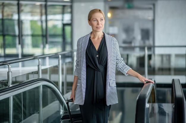 Задумчивая успешная женщина на эскалаторе в аэропорту
