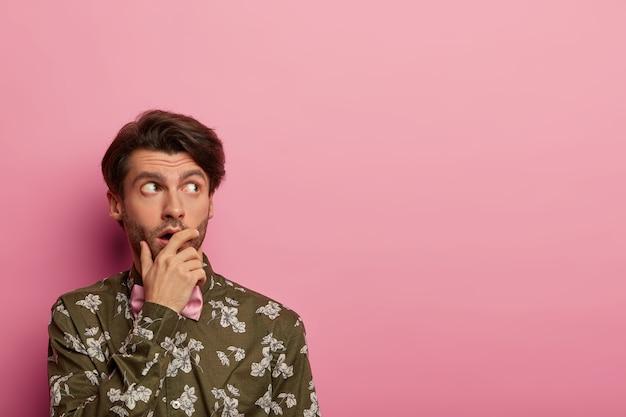物思いにふける驚いた男が口を覆い、脇に集中し、衝撃的な関連性について考え、花柄のシャツを着た