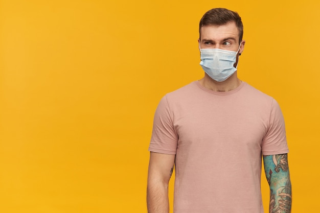 Pensive suspicious young bearded tattooed man in virus protective mask on face against coronavirus with raised brow standing and looking away over yellow wall