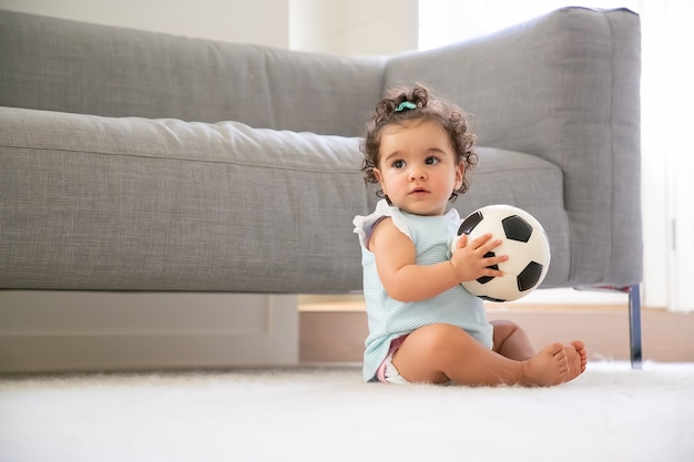 Pensive sweet black haired baby girl in pale blue clothes sitting on floor at home, looking away, playing soccer ball. copy space. kid at home and childhood concept