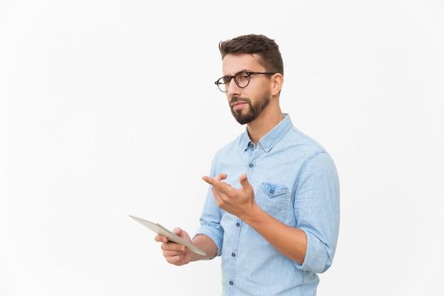 Задумчивый пользователь планшета смотрит и указывает пальцем в сторону