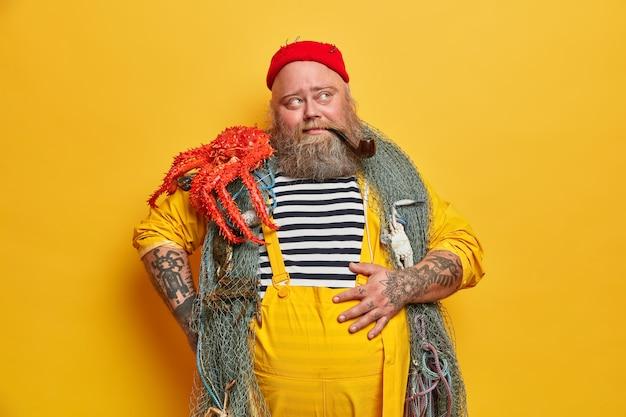 Marinaio tatuato pensieroso tiene la mano sulla pancia, porta la rete da pesca sul collo, il polpo sulla spalla, soddisfatto di una pesca riuscita, si prende una pausa, fuma la pipa