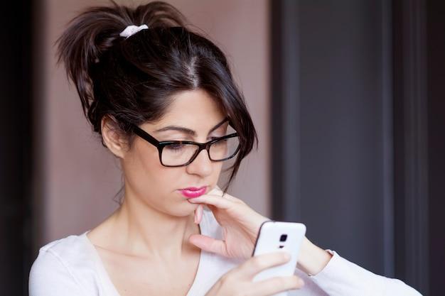 Pensive teen using her mobile