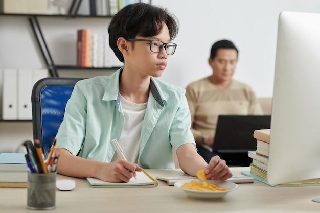 집에서 컴퓨터로 숙제를 할 때 감자 칩을 먹는 생각에 잠긴 10대 소년