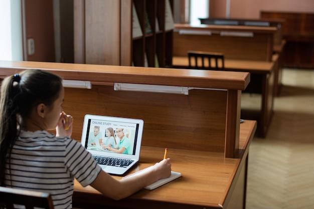 Задумчивая девочка-подросток сидит за столом перед дисплеем ноутбука с домашней страницей веб-сайта удаленного обучения
