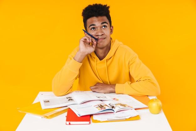 黄色の壁に隔離された教科書と机に座って考えながら勉強している物思いにふけるティーンエイジャーの少年