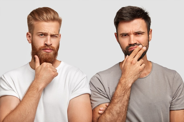 잠겨있는 사려 깊은 집중된 두 남자가 턱을 잡고 올바른 해결책을 찾거나 계획을 세우십시오.