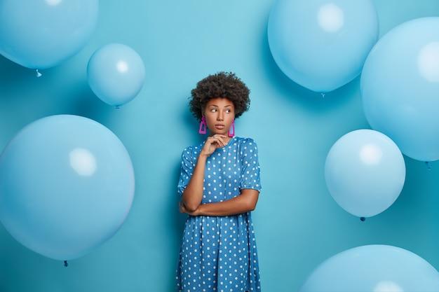 잠겨있는 사려 깊은 어두운 피부의 젊은 여성은 곱슬 머리를 가지고 있고 꿈꾸는 표정으로 옆으로 보이며 여름 휴가 및 축하를 즐기고 실내에 서서 옆으로 보이며 파란색 벽에 포즈를 취합니다.