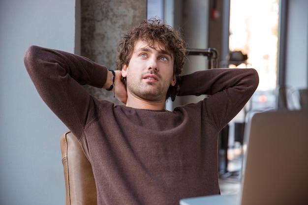 彼の職場に座っている間頭の後ろに手を握って茶色の甘いシャツで物思いにふける思慮深い夢の巻き毛の魅力的なハンサムな男