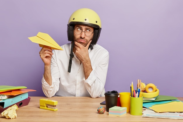 Pensive thoughtful young man tired of working in office, holds paper handmade plane, wears protective helmet, white shirt, holds chin, thinks about changing job position