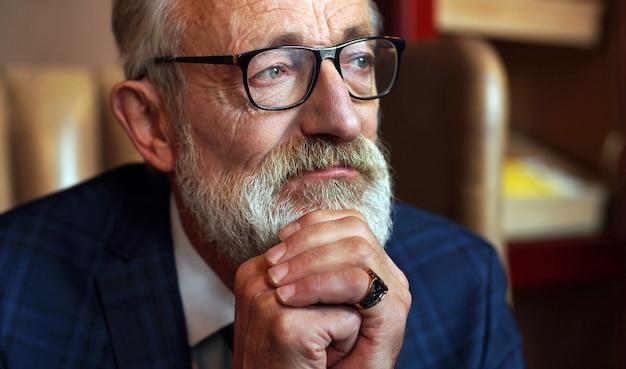 年金受給者、本の作家、シックなオフィスのスリムなスーツを着た灰色のひげを生やした老人、インテリアの物思いに沈んだ、疲れた、残酷な表情