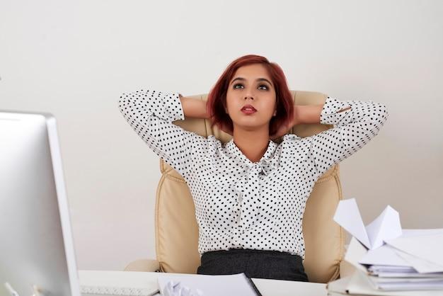 休暇を夢見て彼女のオフィスの椅子に寄りかかって物思いにふける疲れたかなりエレガントな実業家