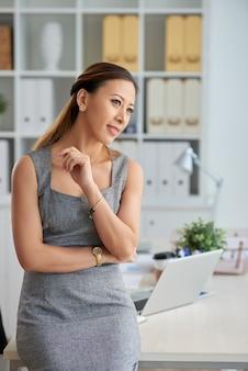 事務用品とテーブルに寄りかかって目をそらしている灰色のドレスを着た物思いにふけるベトナムの女性幹部