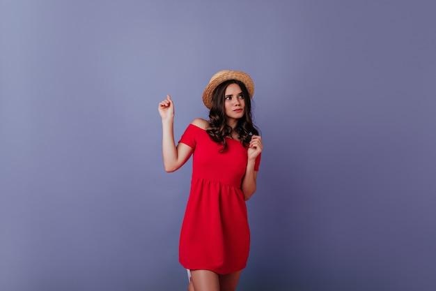 Ragazza ben vestita pensierosa che posa sulla parete viola. attraente donna dai capelli scuri in abito rosso e cappello di paglia che gode del servizio fotografico.